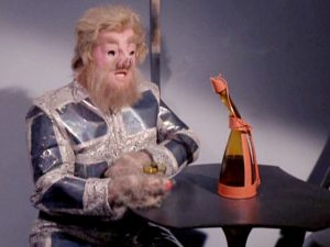 A Tellerite site at a table aboard the Enterprise with with a bottle of Saurian brandy in the TOS episode