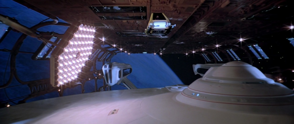 Workbee traveling overhead the U.S.S. Enterprise while she is in dry dock.