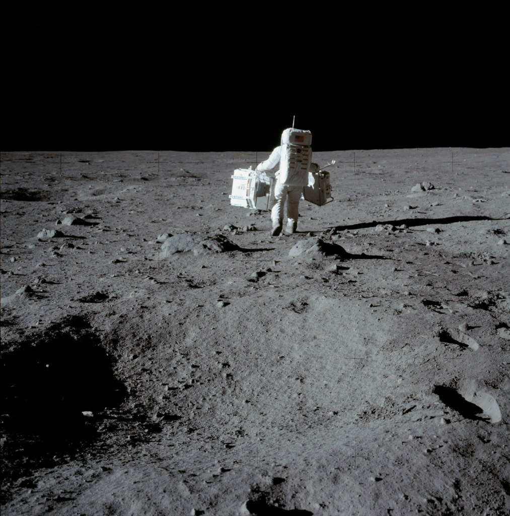 Image of Buzz Aldrin carrying the Passive Seismic Experiment Package (PSEP) in his left hand, and the Laser Ranging Retroreflector Experiment in his right hand, as he head into position for deployment. Taken by Neil Armstrong on the moon, July 20th 1969. (Image courtesy: NASA)
