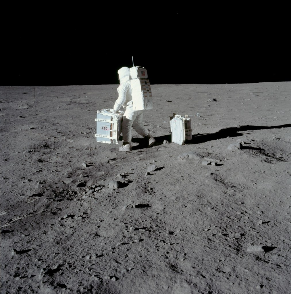 Image of Buzz Aldrin carrying the Passive Seismic Experiment Package (PSEP) into position for deployment. Taken by Neil Armstrong on the moon, July 20th 1969. (Image courtesy: NASA)