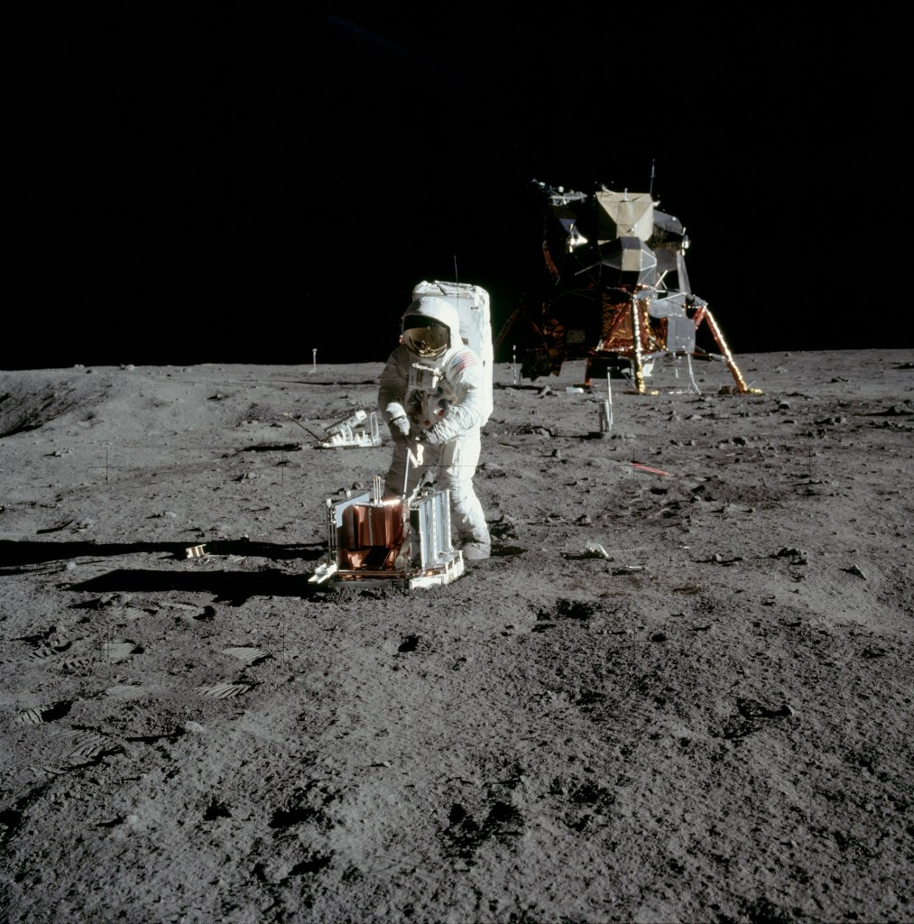 Image of Buzz Aldrin beginning to deploy the Passive Seismic Experiment Package (PSEP) with the Lunar Excursion Module (LEM) in the background, taken by Neil Armstrong on the moon, July 20th 1969. (Image courtesy: NASA)