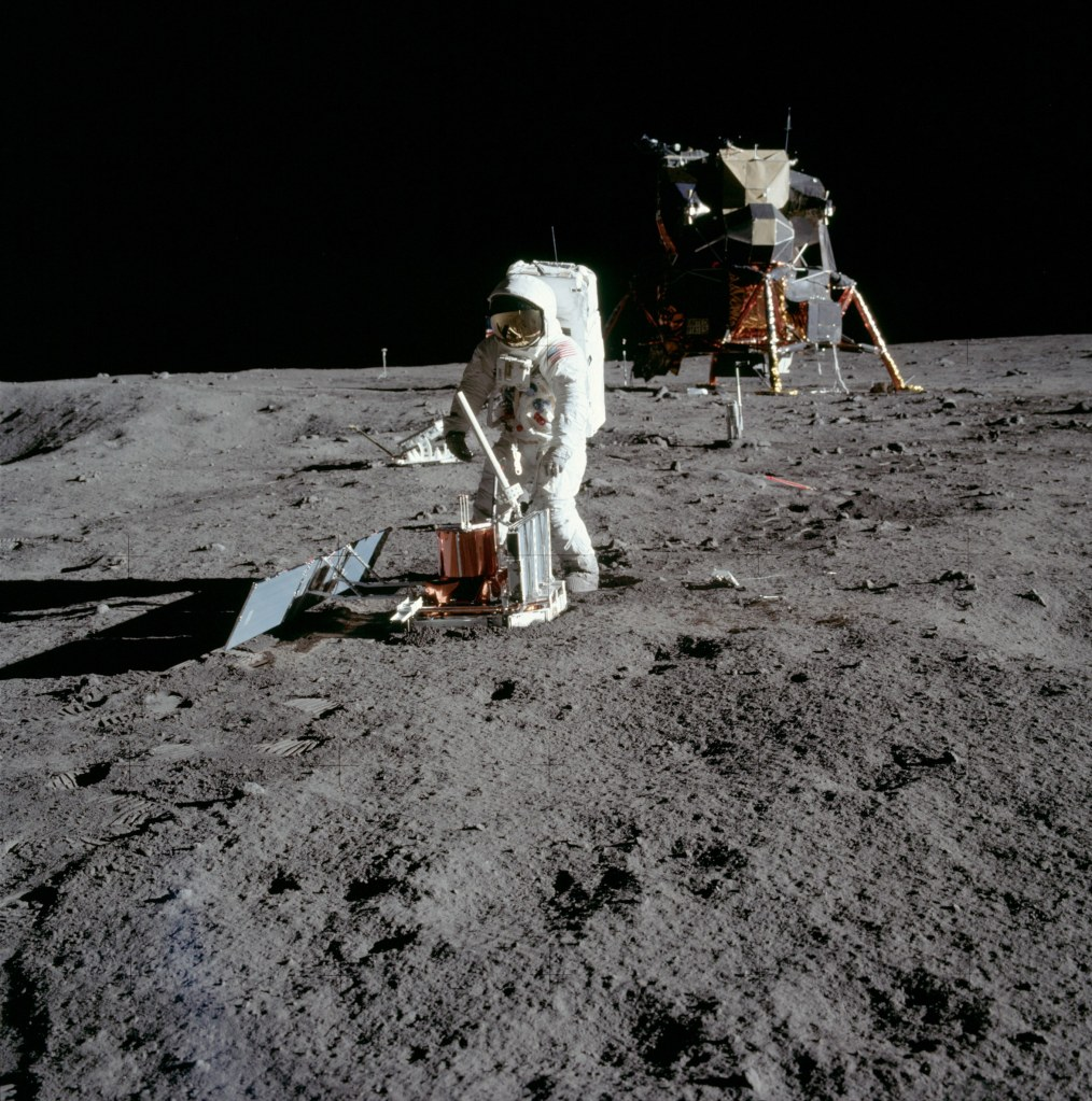 Image of Buzz Aldrin in the process of deploying the Passive Seismic Experiment Package (PSEP) with the Lunar Excursion Module (LEM) in the background, taken by Neil Armstrong on the moon, July 20th 1969. (Image courtesy: NASA)